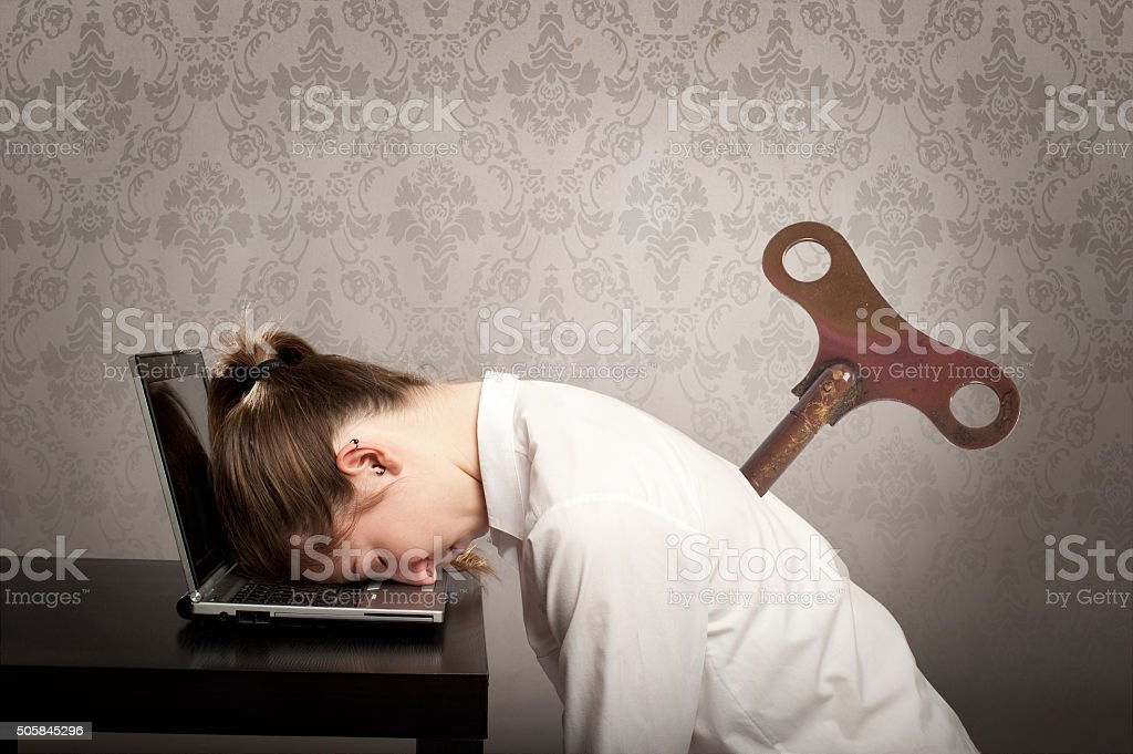 businesswoman with a key winder on her back stock photo