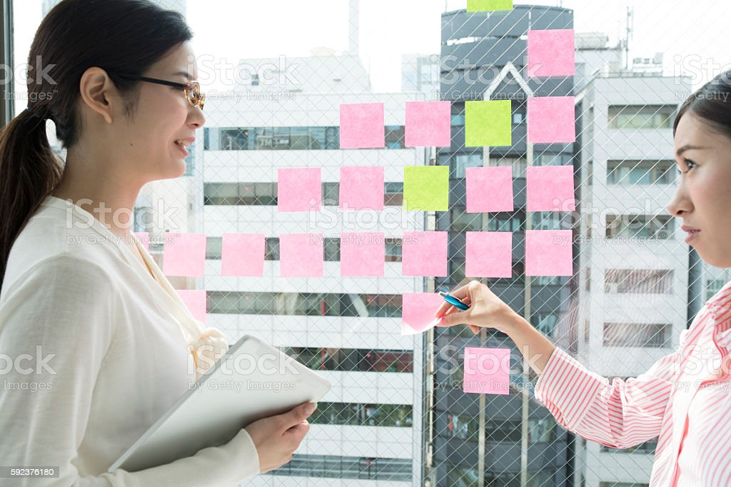 Businesswoman with a meeting while looking at the sticky stock photo