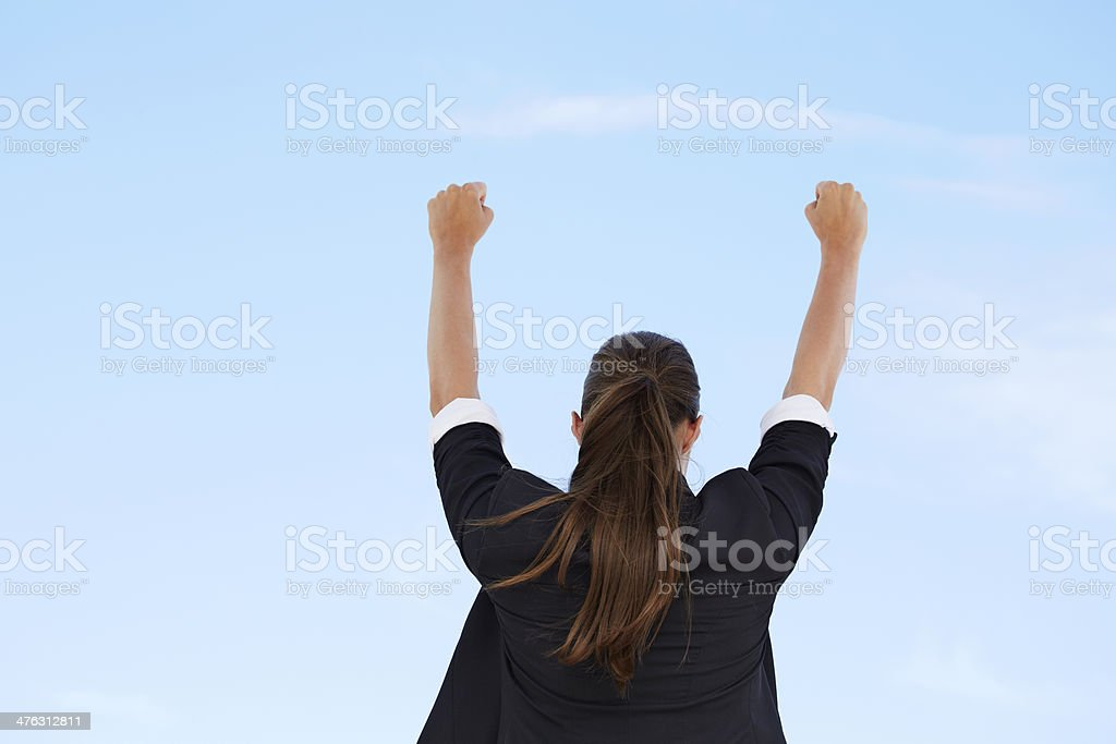 Businesswoman with arms up against blue sky, rear view royalty-free stock photo