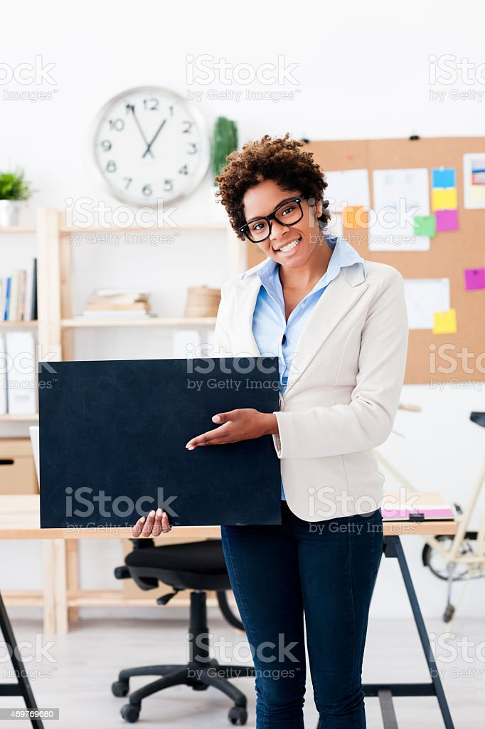 Businesswoman with blank sign at office stock photo