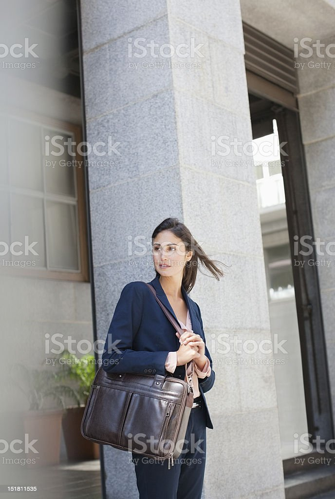 Businesswoman with briefcase in front of urban building royalty-free stock photo