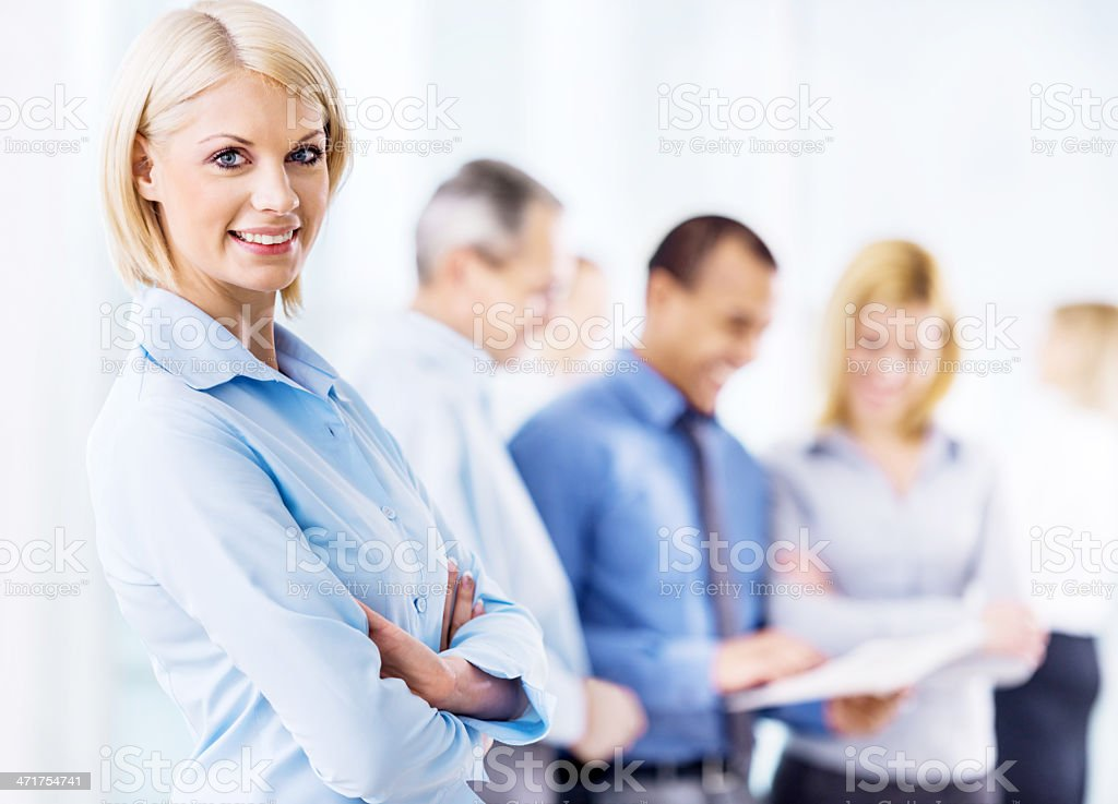 Businesswoman with colleagues in background stock photo