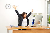 Businesswoman with computer cheering