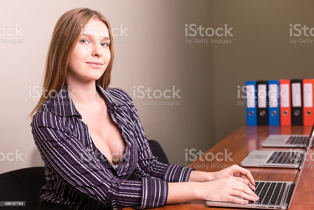 businesswoman with deep neckline working in office stock photo