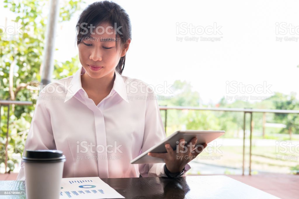 businesswoman with digital tablet & financial summary graph sitting outside office building. young asian woman analyzing investment charts outdoors. business people with coffee in disposable paper cup checking marketing data stock photo