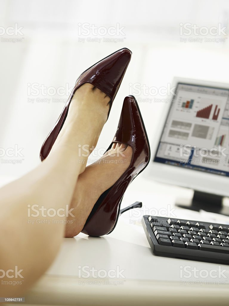 businesswoman with feet on table taking off shoes royalty-free stock photo