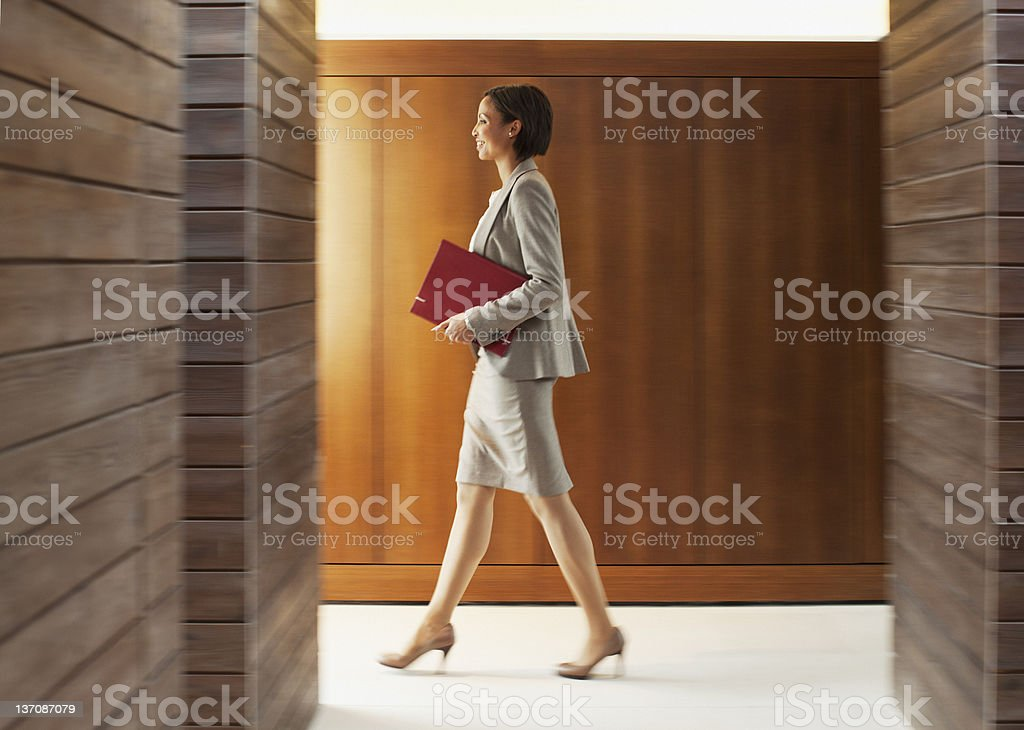 Businesswoman with folder walking in office corridor stock photo