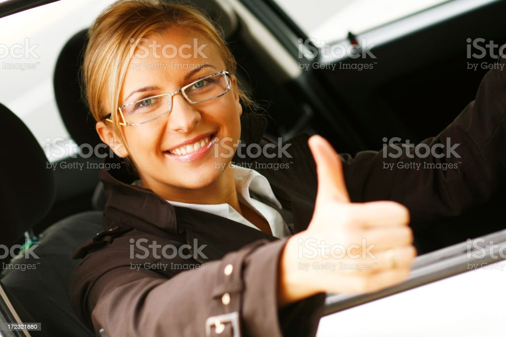 Businesswoman with glasses giving the thumbs up stock photo