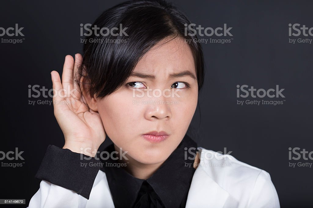 Businesswoman with hand behind her ear and listens carefully stock photo