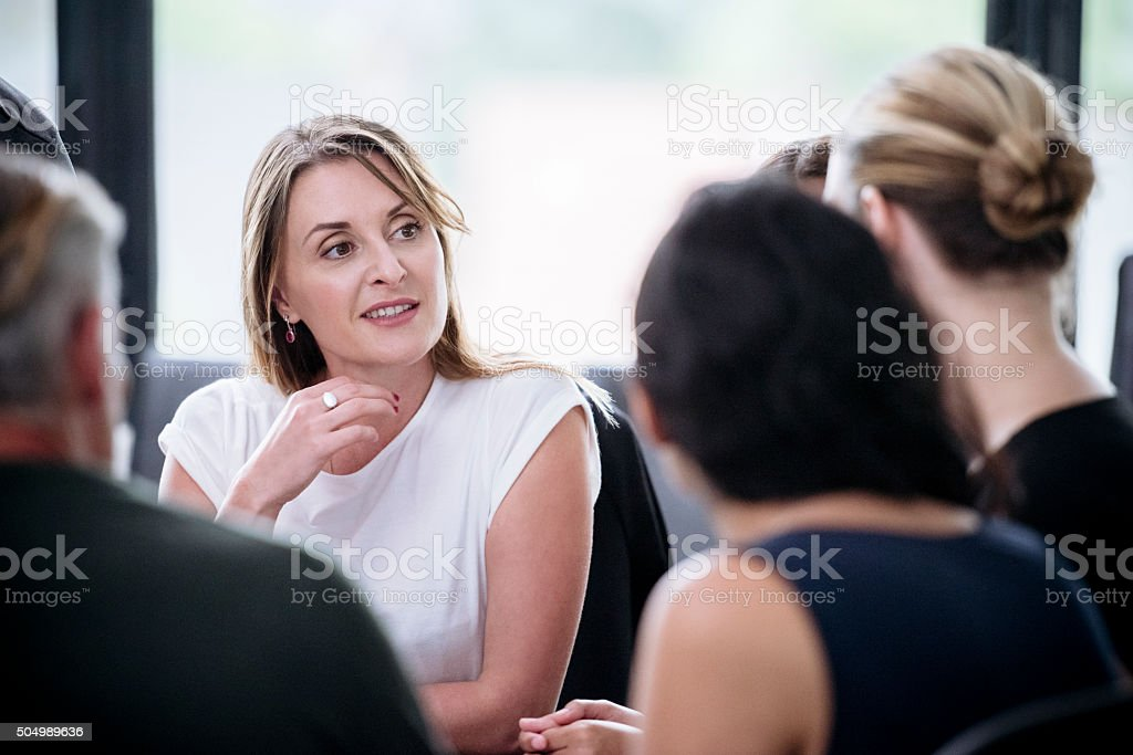 Businesswoman with hand on chin listening to colleague in meeting stock photo