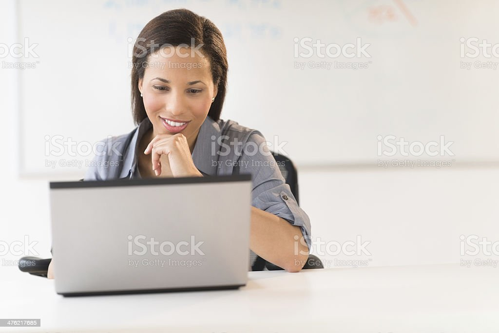Businesswoman With Hand On Chin Using Laptop At Desk stock photo