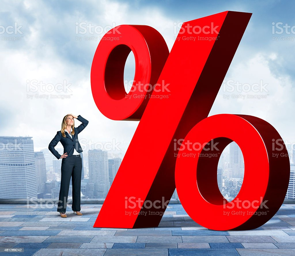 Businesswoman With Hand On Head Looking Up At Percentage Sign stock photo