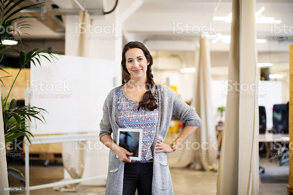 Businesswoman with hand on hip holding digital tablet stock photo
