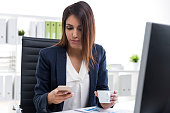 Businesswoman with her cell phone and a cup of coffee