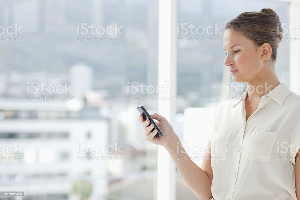 Businesswoman with her cellphone standing at the window stock photo