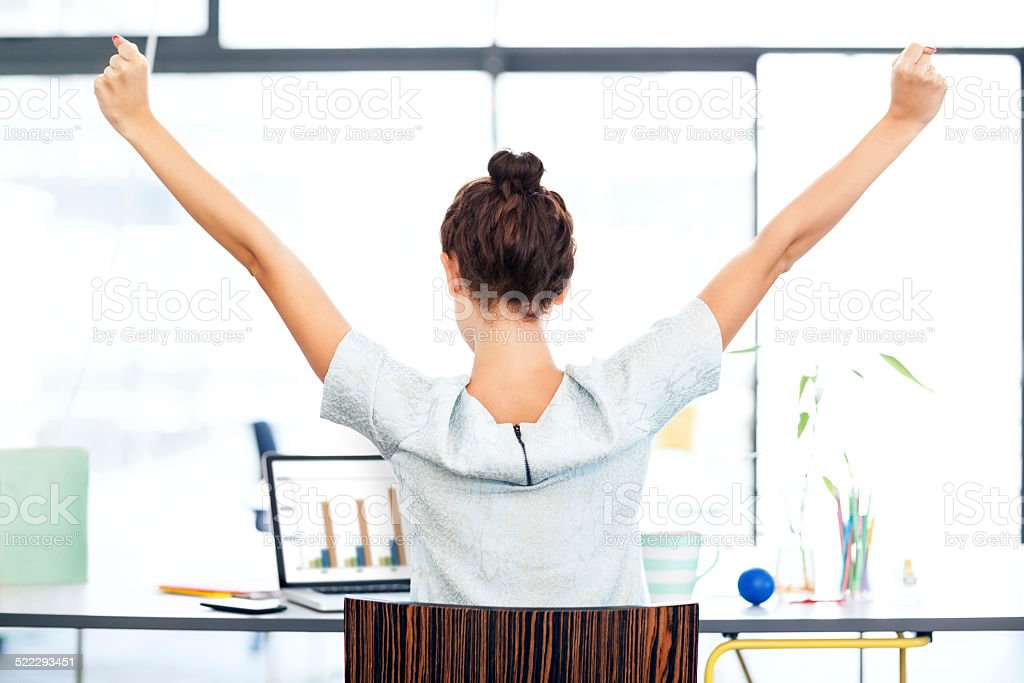 Businesswoman With Laptop Celebrating Success At Office Desk stock photo