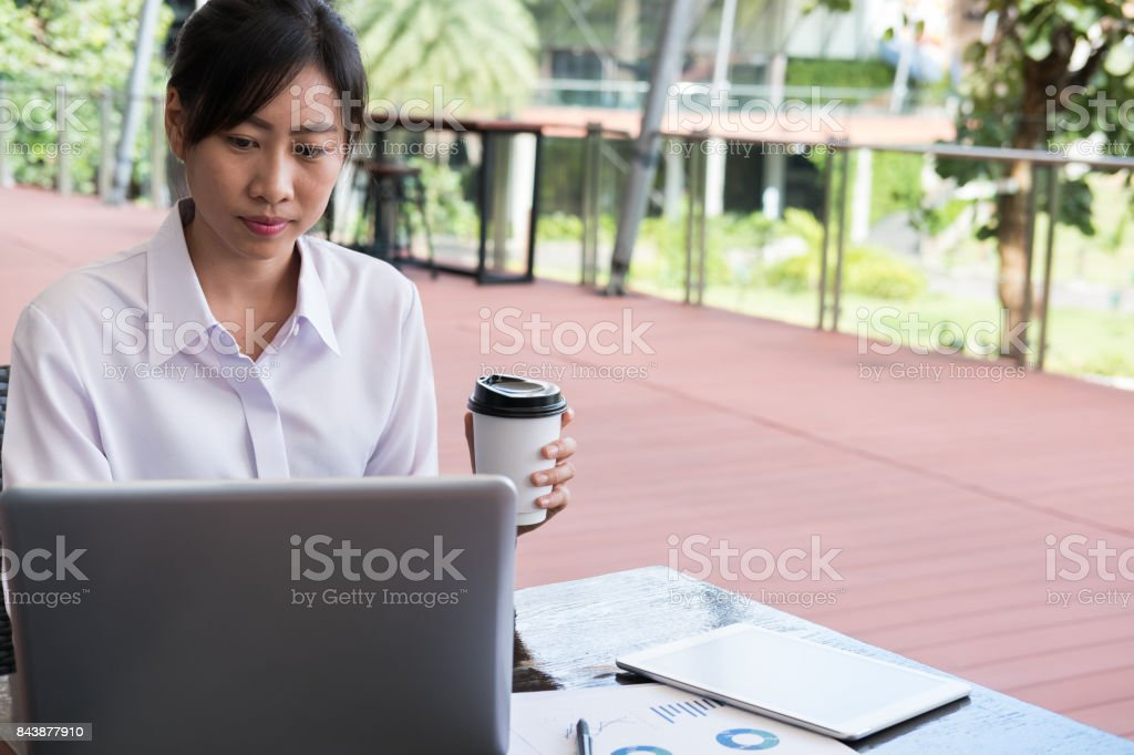 businesswoman with laptop computer & financial summary graph sitting outside office building. young asian woman analyzing investment charts outdoors. business people with coffee in disposable paper cup checking marketing data stock photo