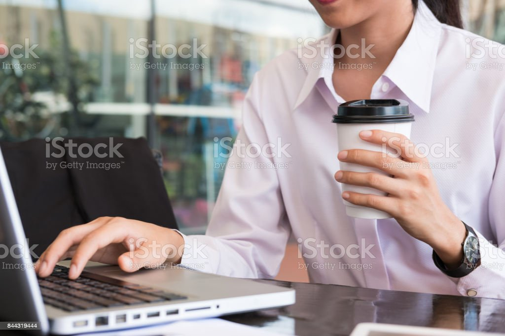 businesswoman with laptop computer sitting outside office building. young asian woman analyzing investment charts outdoors. business people with coffee in disposable paper cup working with marketing data online. stock photo