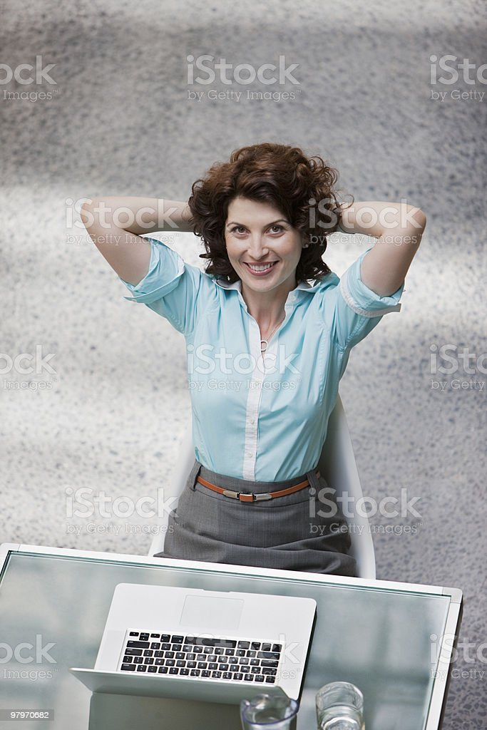 Businesswoman with laptop sitting with hands behind head royalty-free stock photo