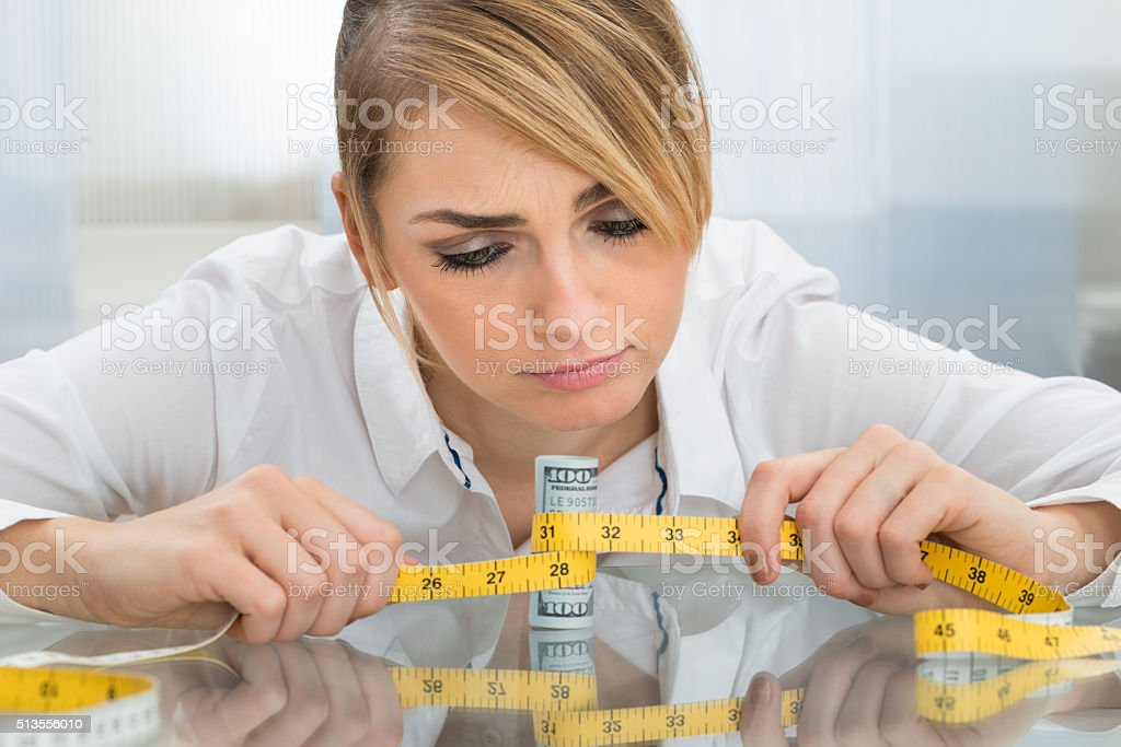Businesswoman With Measuring Tape And Banknote stock photo