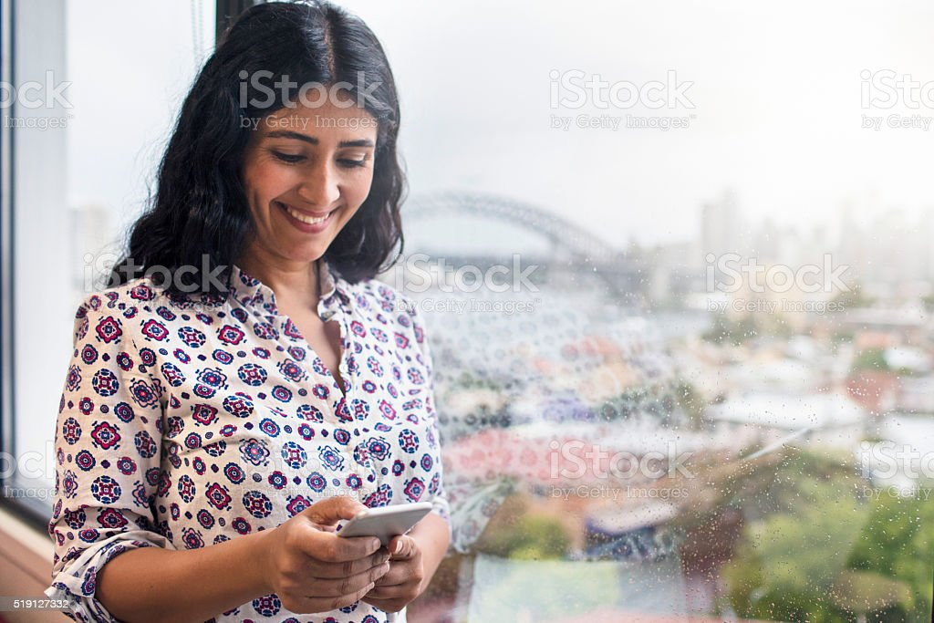 Businesswoman with mobile phone in the office stock photo