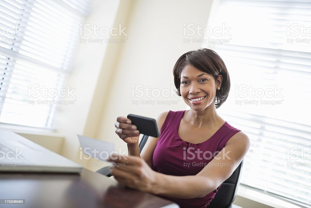 Businesswoman With Phone Depositing check stock photo