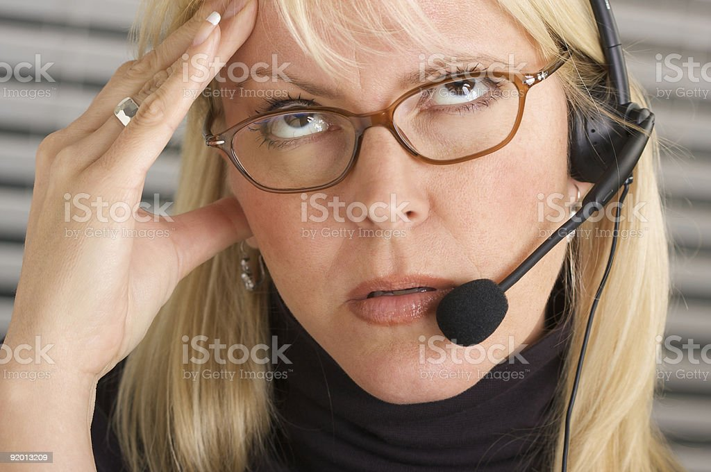 Businesswoman with Phone Headset and Headache royalty-free stock photo