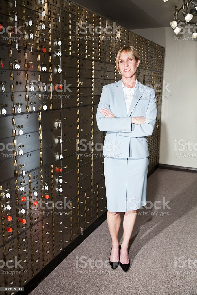 Businesswoman with safety deposit boxes royalty-free stock photo