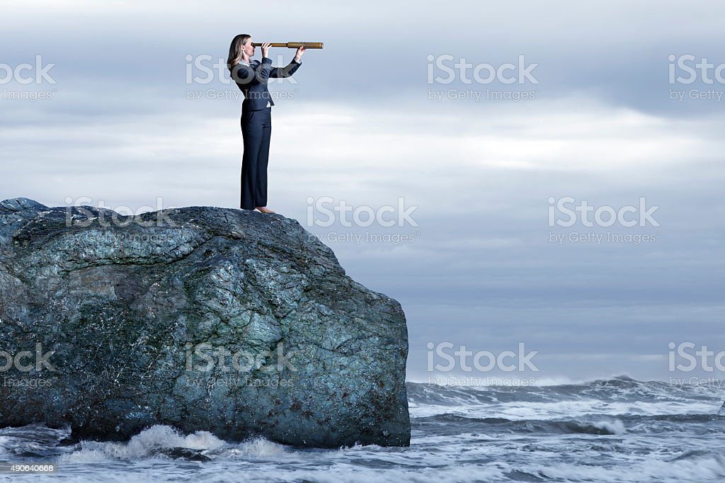 Businesswoman With Spyglass Looking Out To Rough Seas stock photo