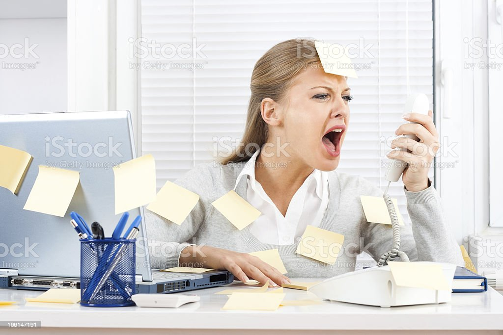 A businesswoman with sticky notes all over her body yelling stock photo
