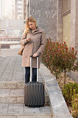 Businesswoman with suitcase and phone standing on street