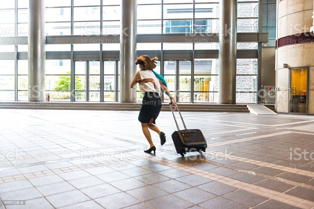 Businesswoman with Suitcase Running in hall stock photo
