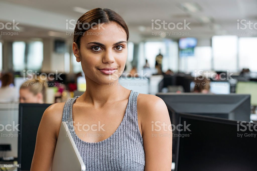 Businesswoman with tablet smiling towards camera in modern office stock photo