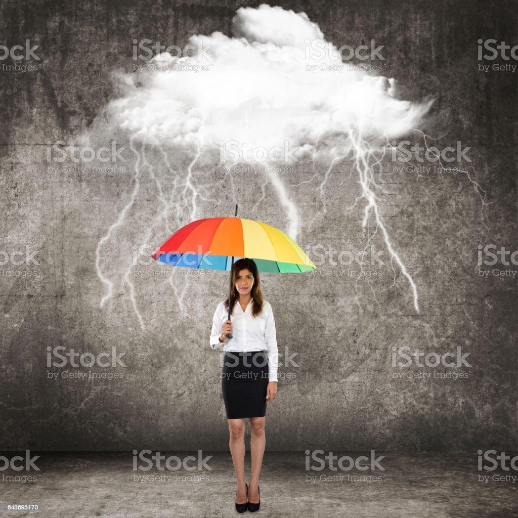 Businesswoman with umbrella under thunderstorm cloud stock photo