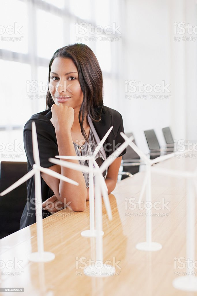 Businesswoman with wind turbine models in office royalty-free stock photo