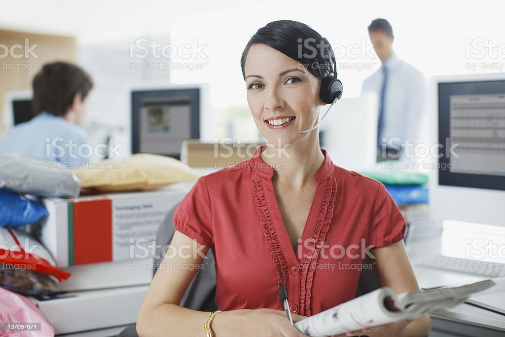 Businesswoman working at desk in headset stock photo