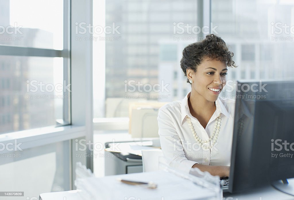 Businesswoman working at desk in office stock photo