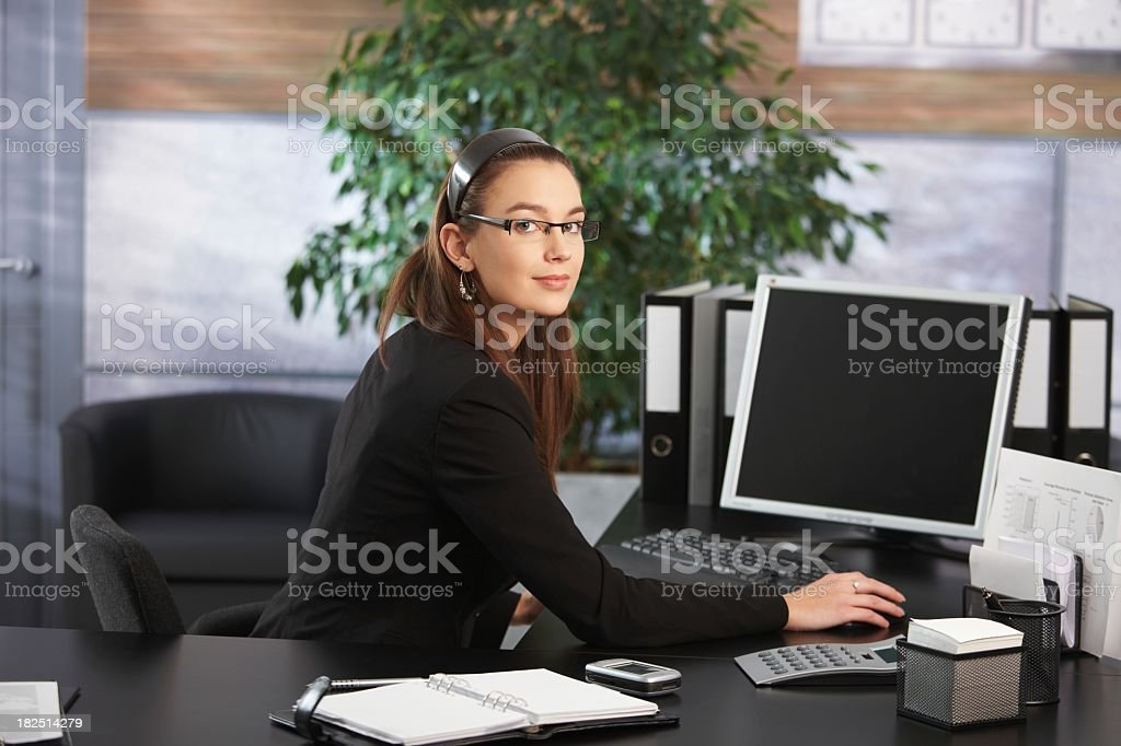 A businesswoman working at her desk in her office royalty-free stock photo