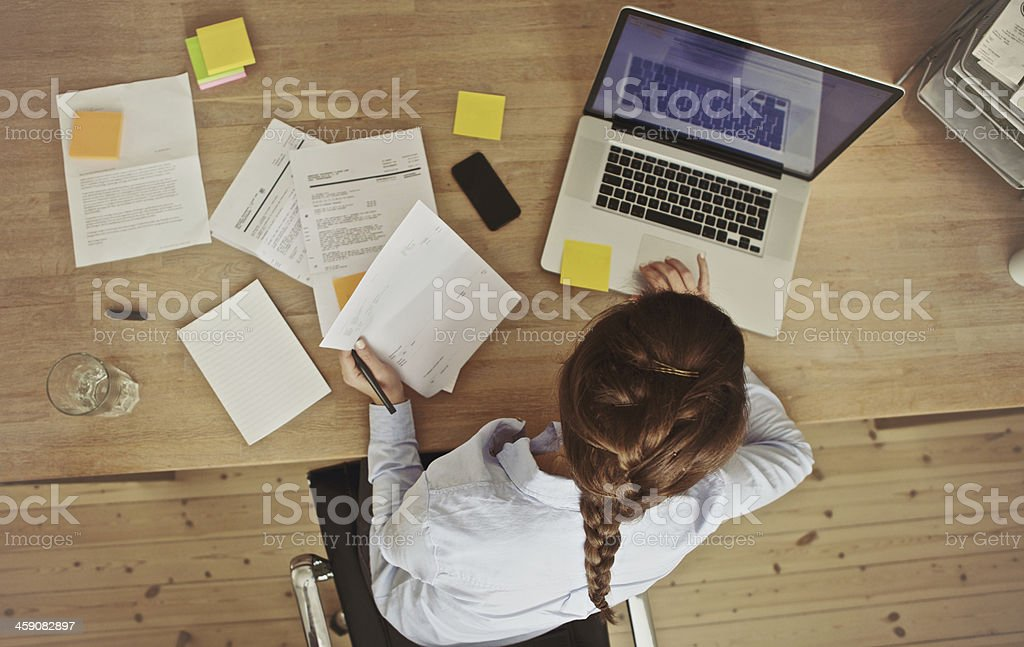 Businesswoman working at her office desk with documents and laptop stock photo