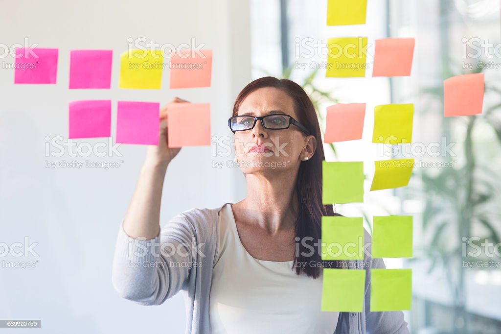 Businesswoman working from sticky notes. stock photo