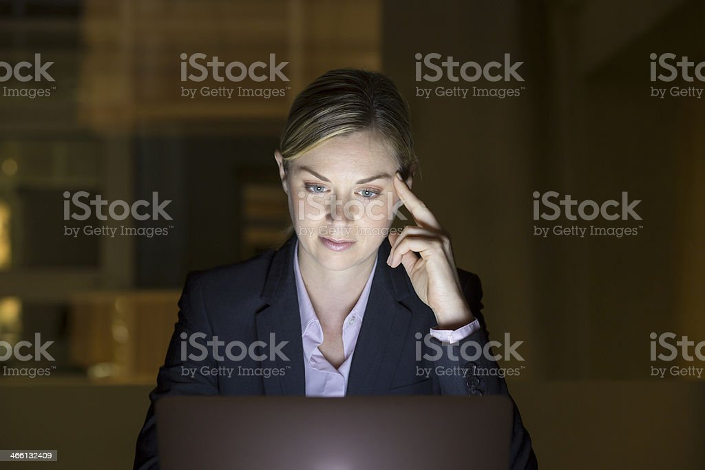 Businesswoman working late in her office on laptop, night light royalty-free stock photo