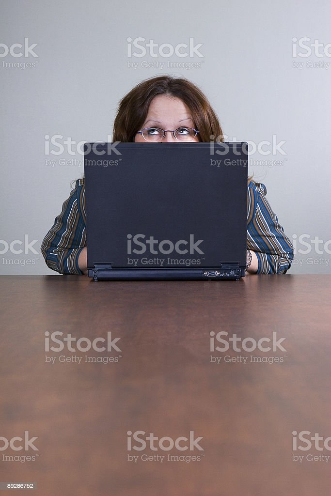 Businesswoman working on a laptop with pensive look royalty-free stock photo