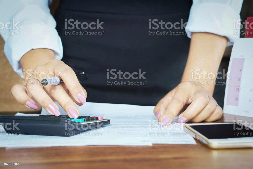 businesswoman working on calculator with mobile phone on desk stock photo