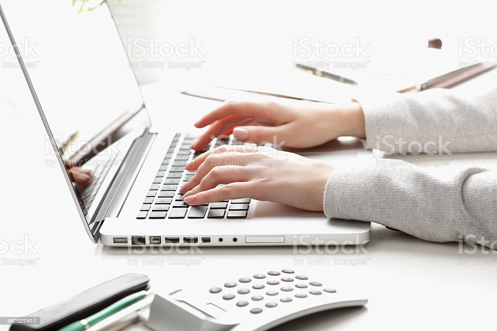 Businesswoman working on laptop and calculating data stock photo