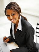 Businesswoman working on laptop and smiling