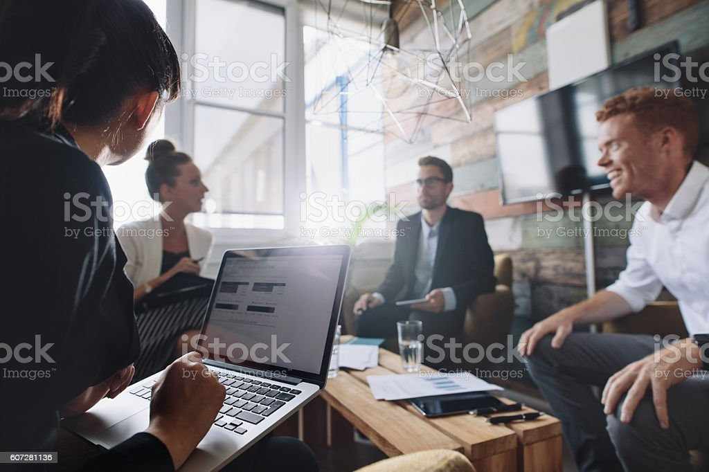 Businesswoman working on laptop in meeting stock photo