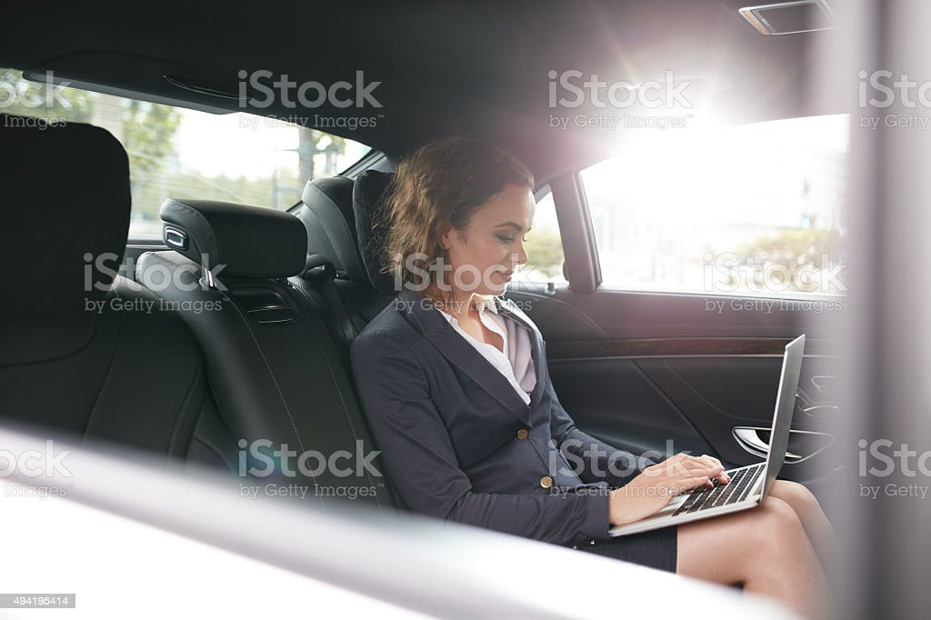 Businesswoman working on laptop inside a car stock photo