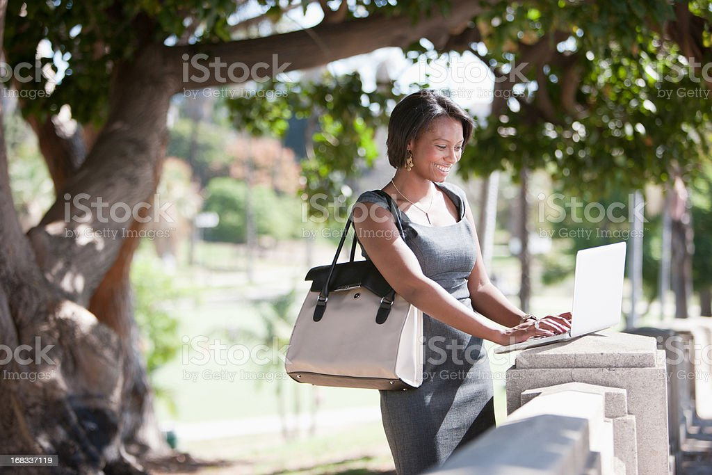 Businesswoman working on laptop outdoors royalty-free stock photo
