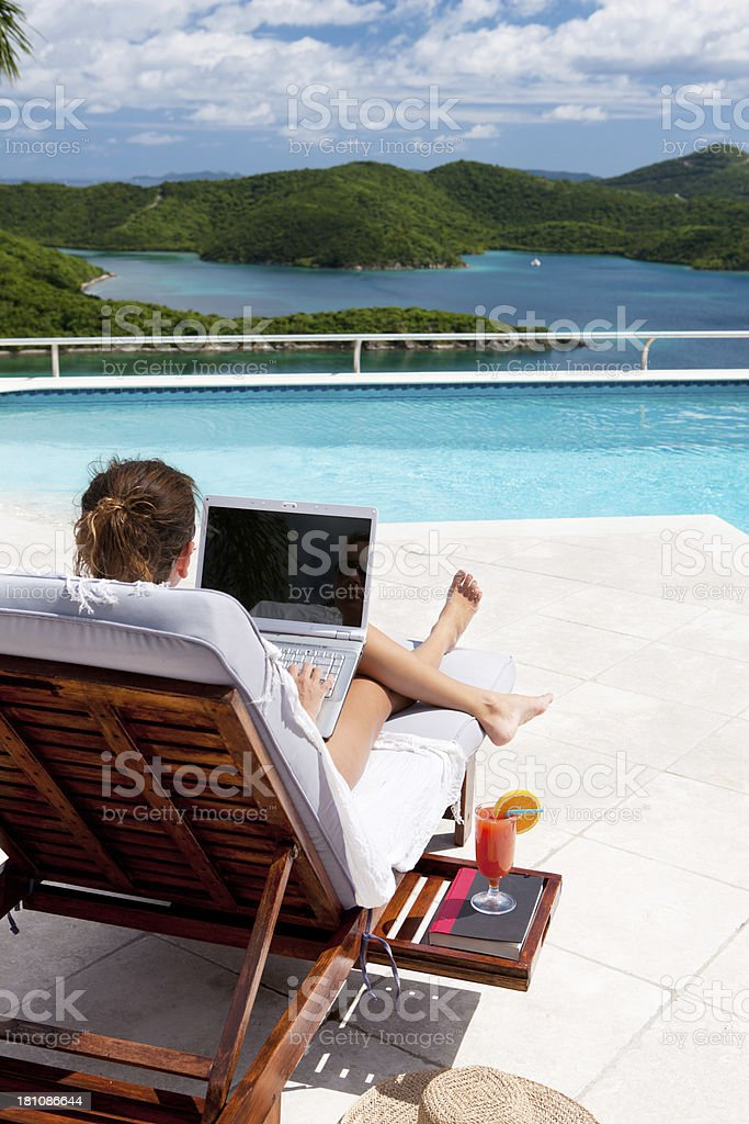 businesswoman working on laptop while sunbathing at the pool royalty-free stock photo