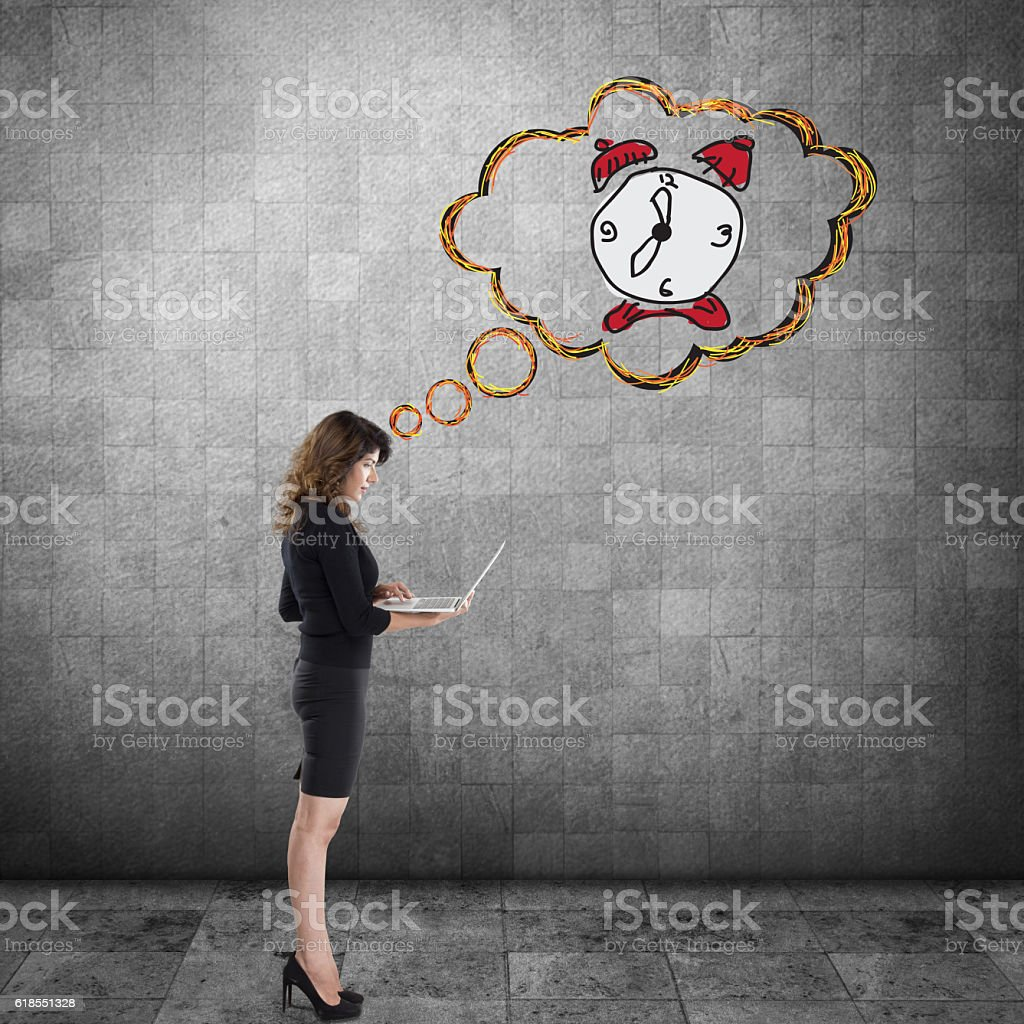 Businesswoman working on laptop with clock stock photo